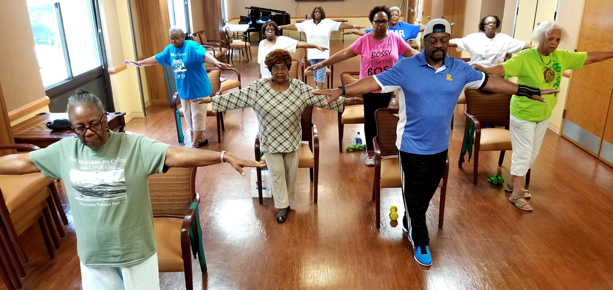 Group of seniors with arms stretched out doing a falls prevention exercise