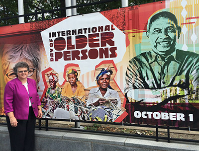 Photo of Kathy Greenlee at a mural near the UN showing 'International Day of Older Persons, October 1'