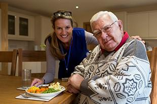Woman serving meal to older man at home